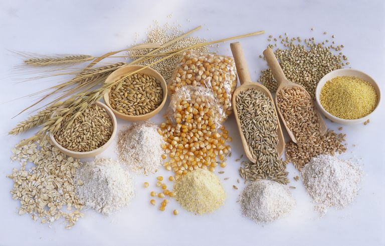Assorted cereals, flour and grains in piles, bowls and scoops