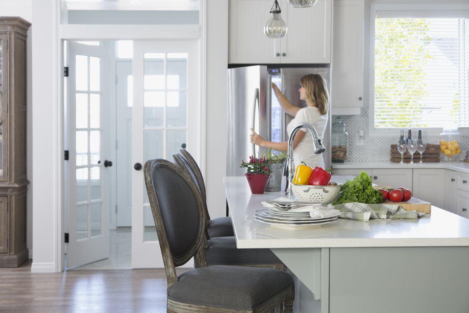 Woman opening freezer door in kitchen