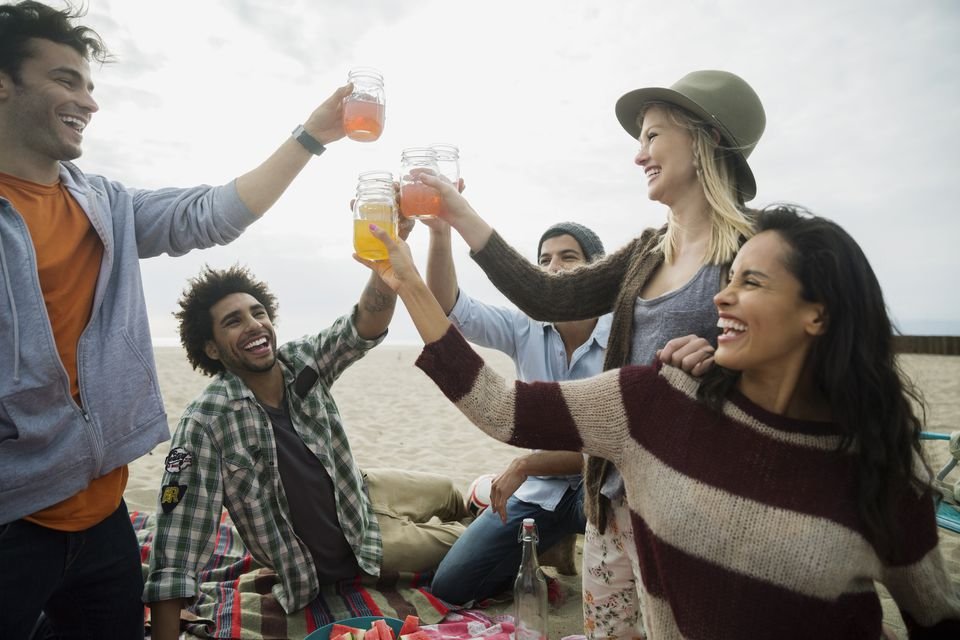 Friends toasting cocktails on beach