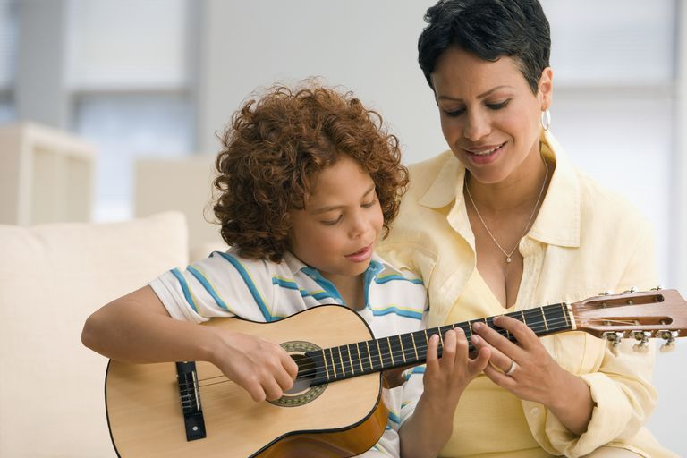 Mother helping son play guitar