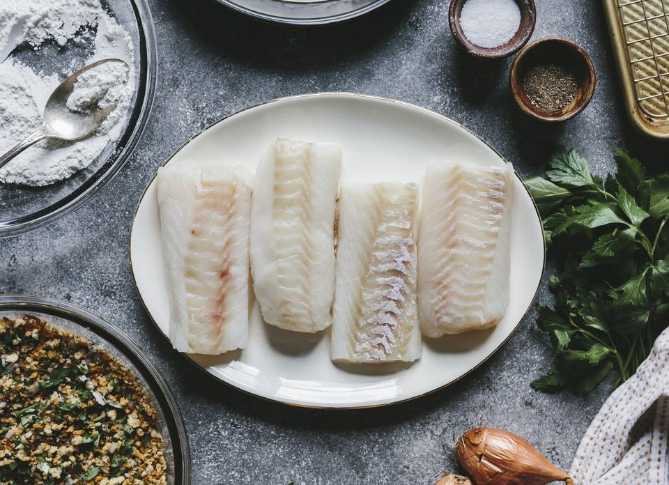 Four cod fillet and the rest of the ingredients for oven fried fish fillets are photographed from the top.