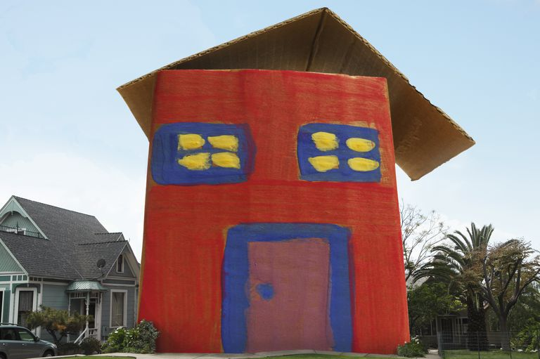 full-sized red, blue, and yellow cardboard house in a neighborhood