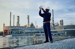 Worker gathering water samples at chemical plant
