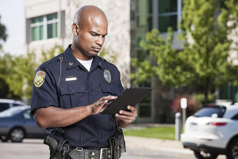 Police Officer Using Computer Tablet A mid...