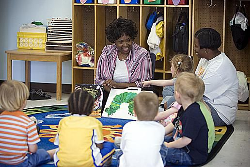 Joycelyn Harrison reads to seven children in the stegasaurus room.