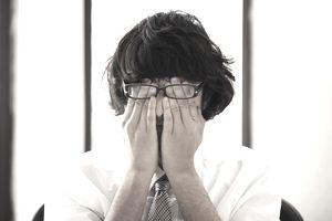 man rubbing his eyes at work