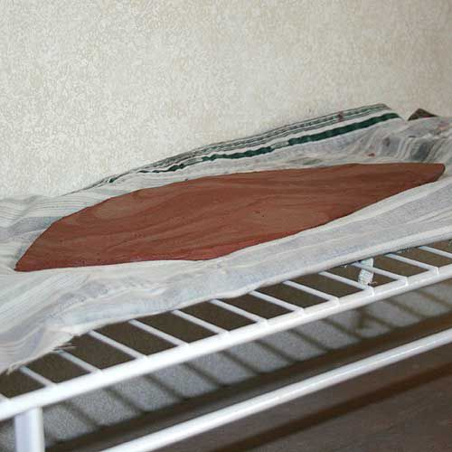 A clay slab drying on a wire rack, which allows evaporation to take place from all surfaces.