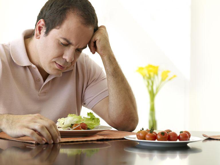 Sad man eating a salad