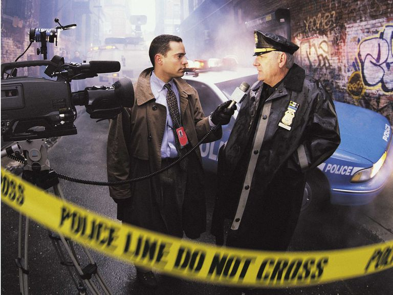 A picture of a reporter interviewing a policeman