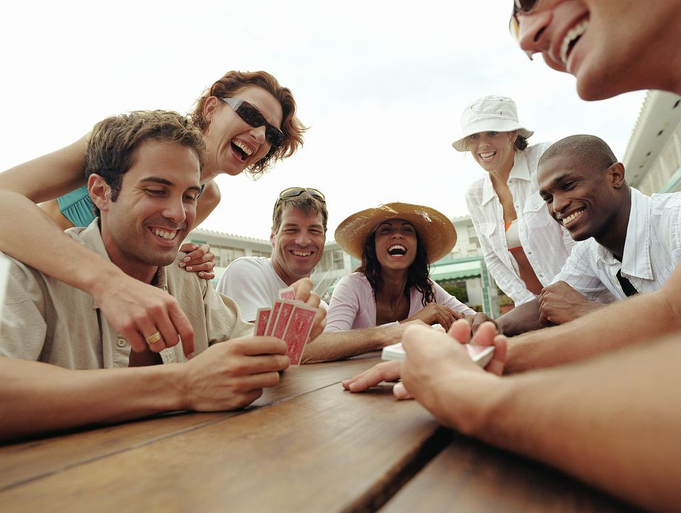 Group of adults playing cards by poolside of hotel