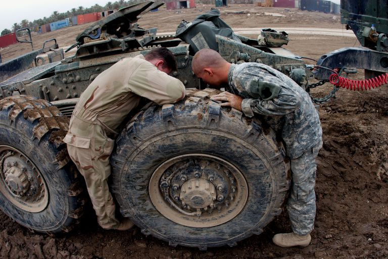 Two soldiers working on vehical
