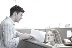 Woman in cubicle talk to male coworker