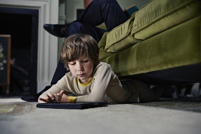 Boy on tablet computer under sofa