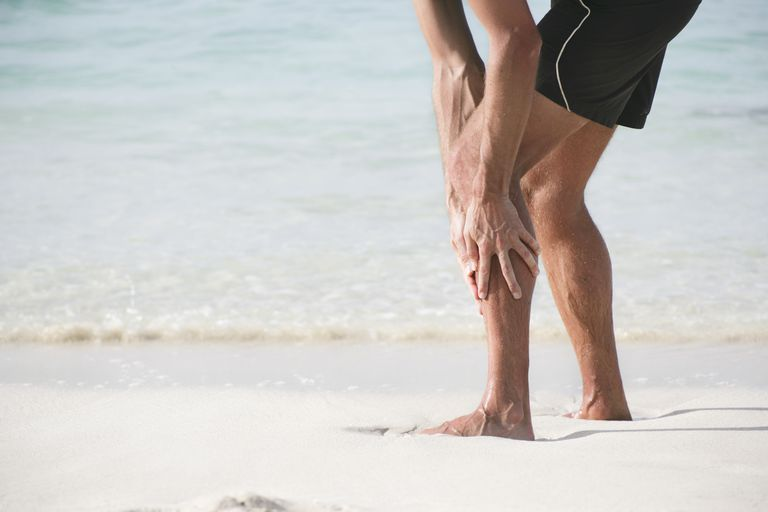 Runner on beach holding lower leg in pain
