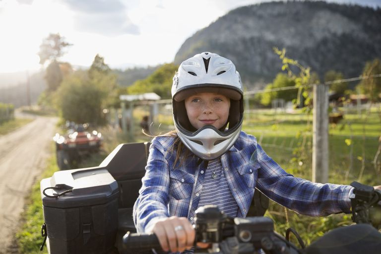 Smiling girl wearing helmet driving quadbike on rural farm