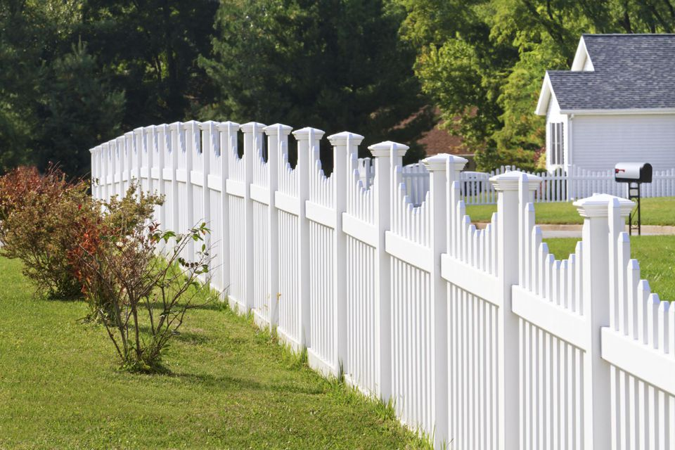 Ornate white vinyl fence running across a yard with house and trees in the background.