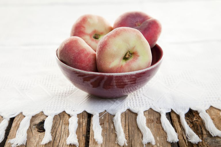 Vineyard peaches in bowl on white cloth, close-up