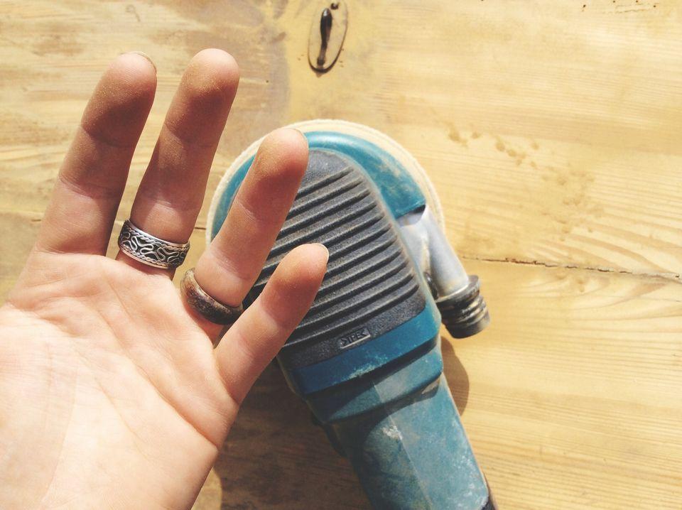 Hand next to palm sander