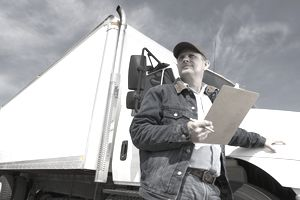 A truck driver holding a clipboard and leaning against his delivery truck.