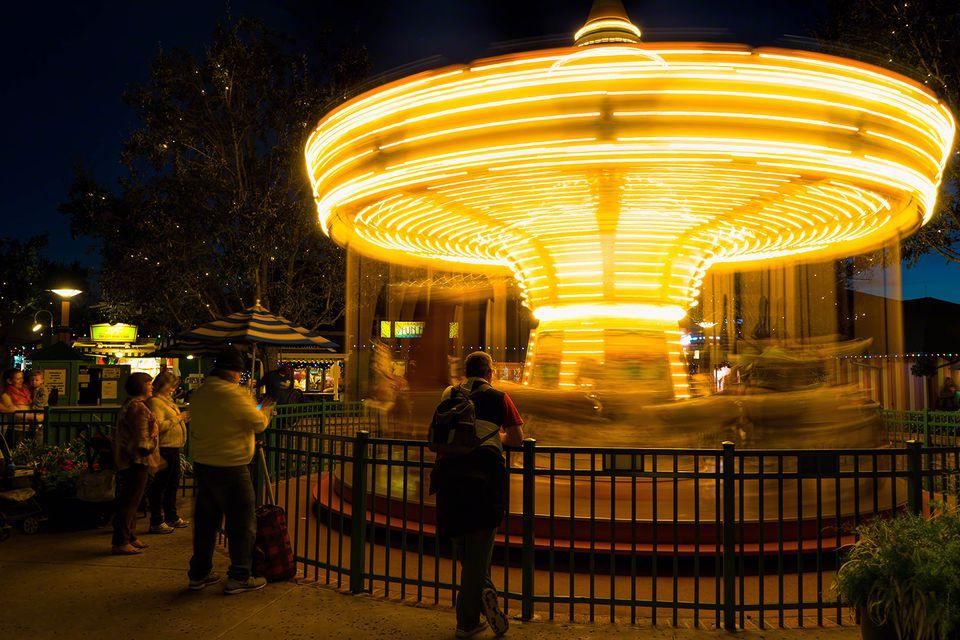 People Looking At Illuminated Carousel At Disney World At Night