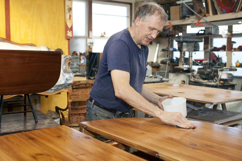 Man working in his shop refurbishing wood