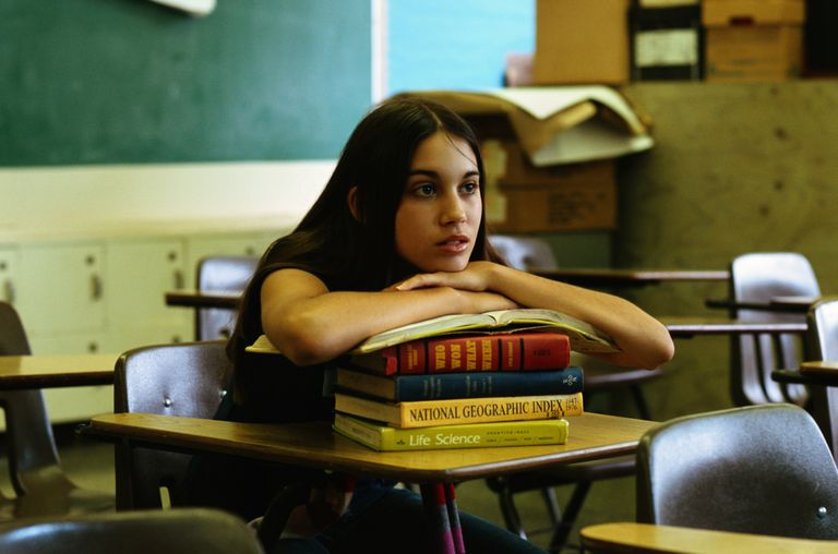 Student resting on books in classroom