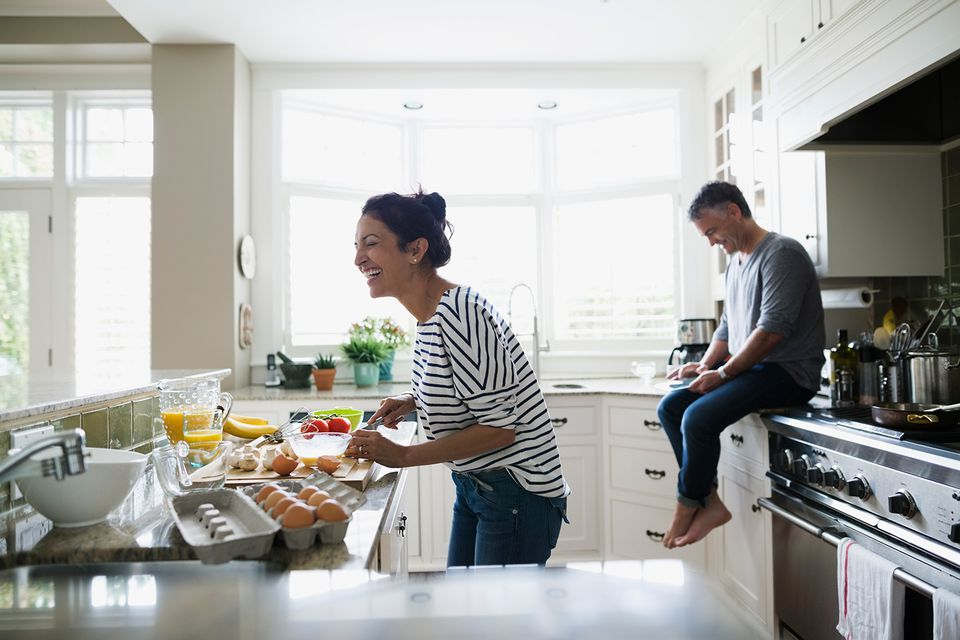 Laughing couple preparing breakfast in kitchen