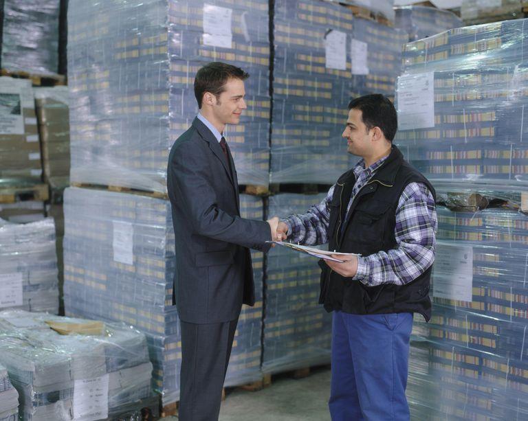 men shaking hands in warehouse