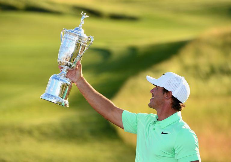 Brooks Koepka holds the trophy aloft after winning the 2017 US Open
