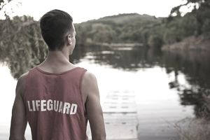 teen boy lifeguard looking over lake