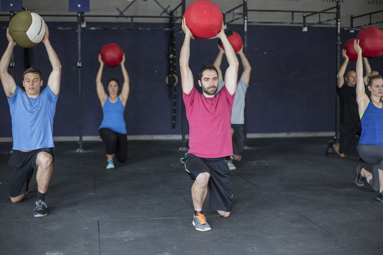 exercise class doing overhead lunges