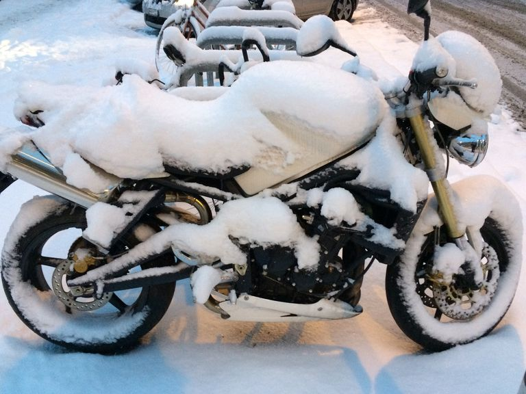 Close-Up Of Snowcapped Motorcycle Parked On Sidewalk During Winter