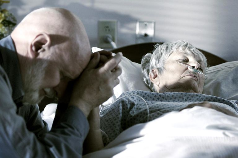 elderly man visits and prays over his wife in a hospital bed