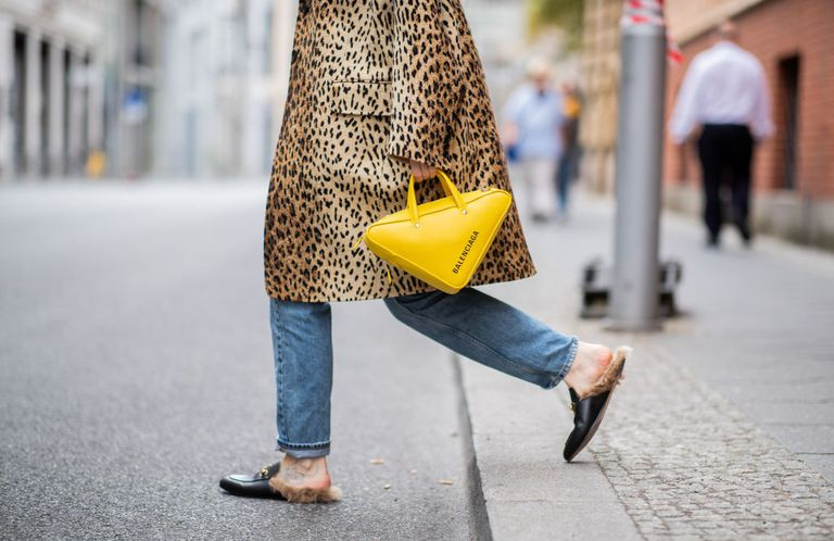 Woman in leopard coat yellow purse and loafers with fur