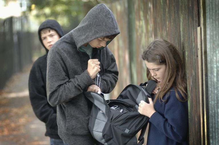 Two teenage boys (14-15) in hoods stealing items from school girl's bag (12-13)