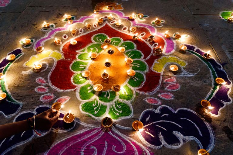 Woman arranging oil lamps on rangoli during Diwali.