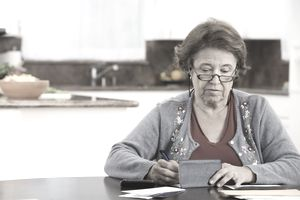 Woman writing checks in kitchen
