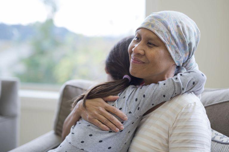 Ethnic adult female cancer patient hugging her granddaughter