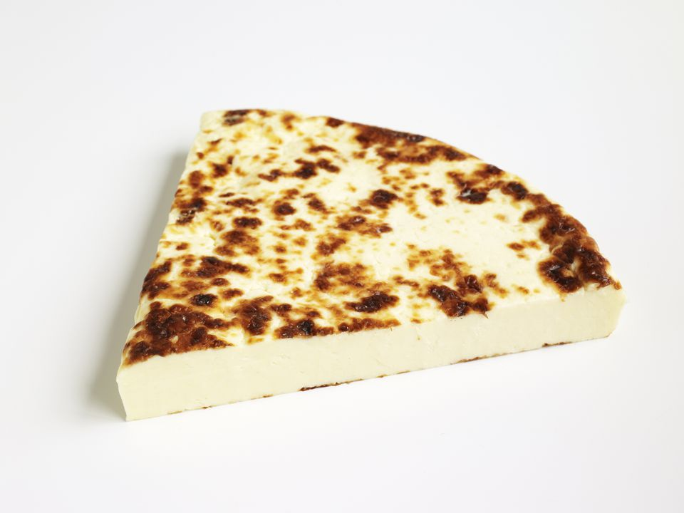 Slice of Juustoleipa cow or reindeer milk cheese with lightly toasted rind, made in Finland and Lapl