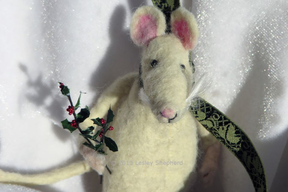 Holly branches in the paw of a 1:24 scale mouse figure.