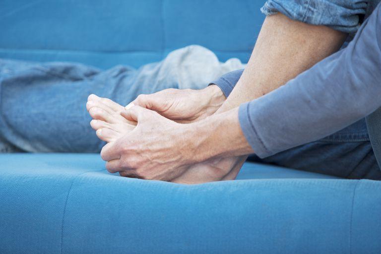 man looking at injured toenail