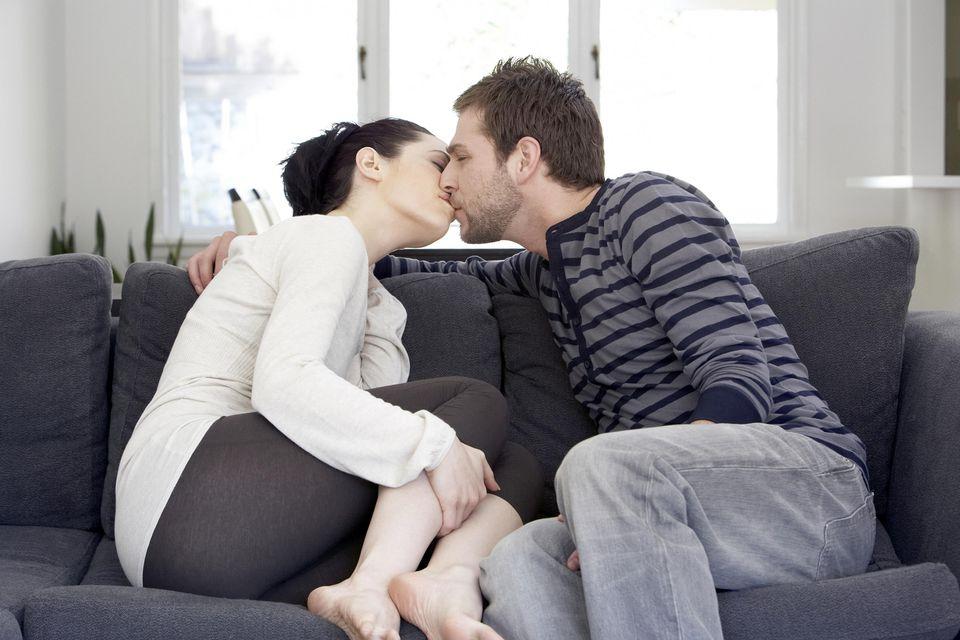 Couple kissing on sofa