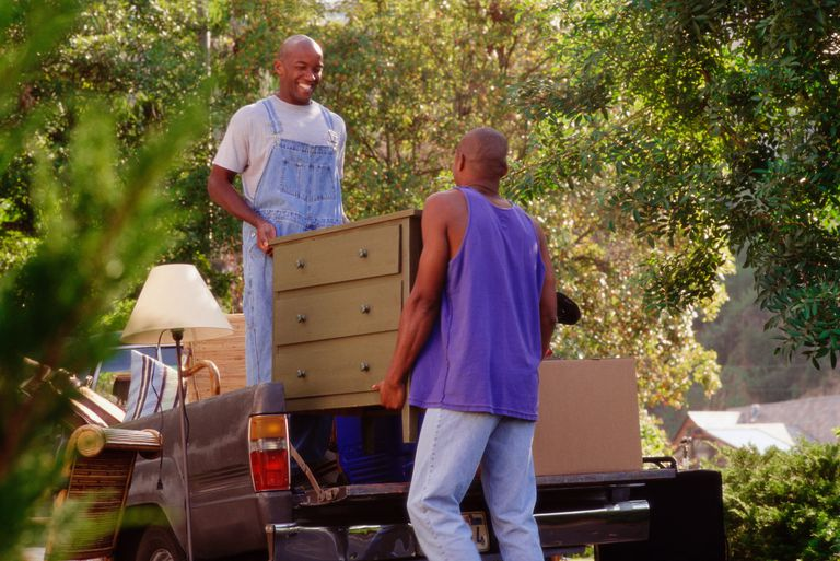 Two young men loading chest of drawers onto truck