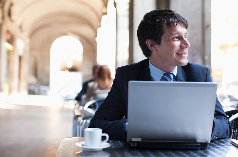 Businessman using laptop in sidewalk cafe