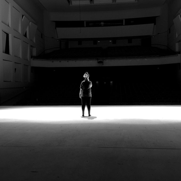 Rear View Of Woman Standing On Illuminated Stage In Auditorium