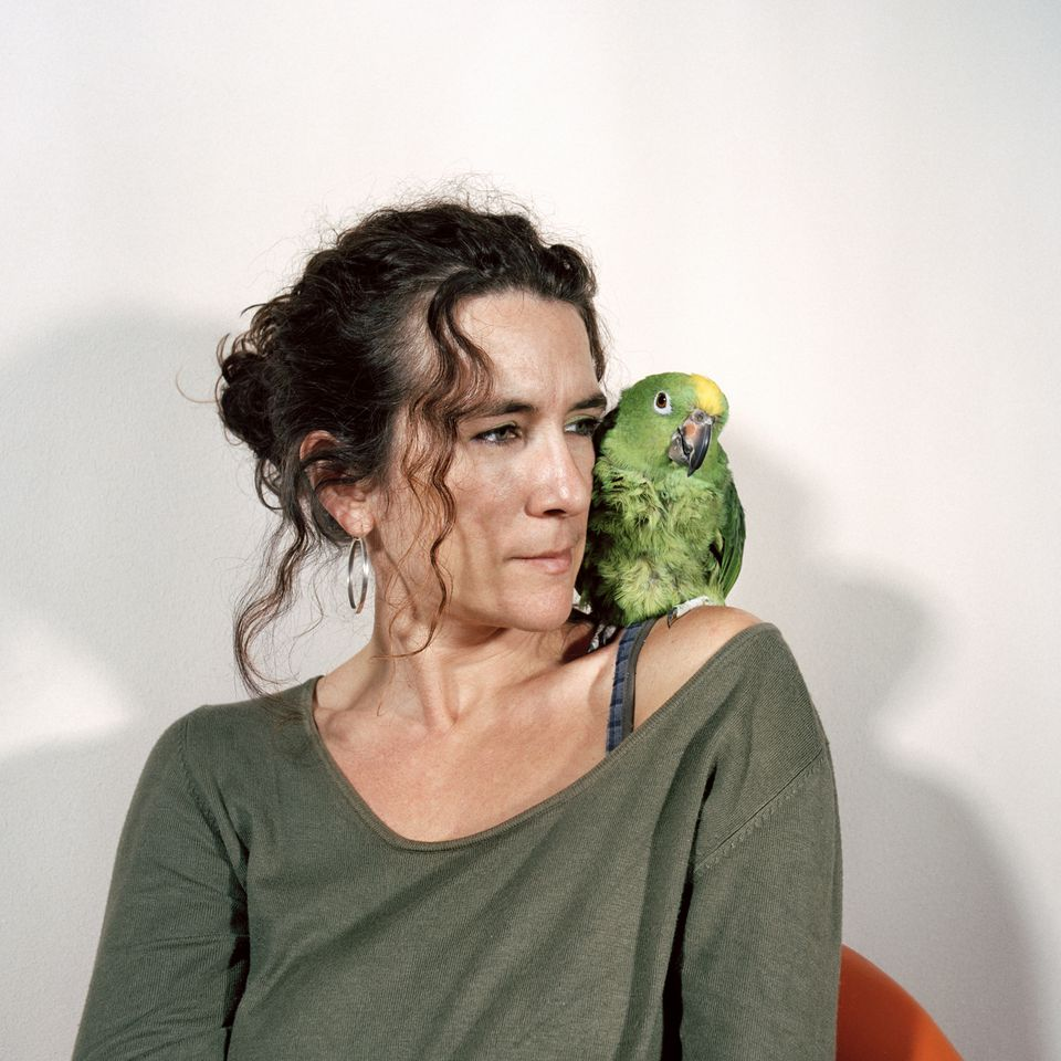 Woman with yellow-crowned parrot on shoulder