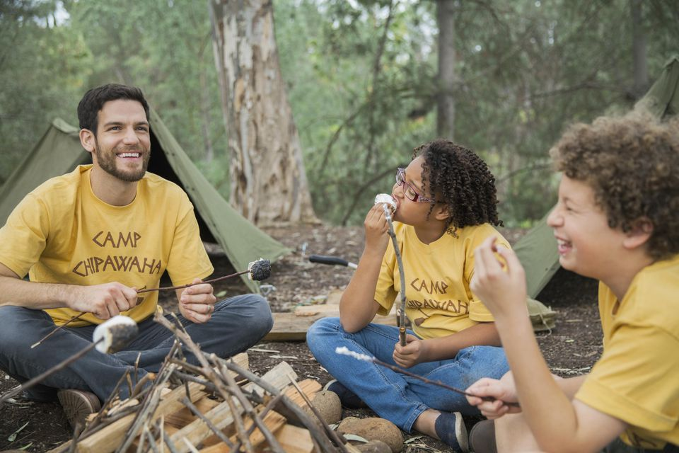 A picture of a happy camp counselor and children with marshmallows around campfire