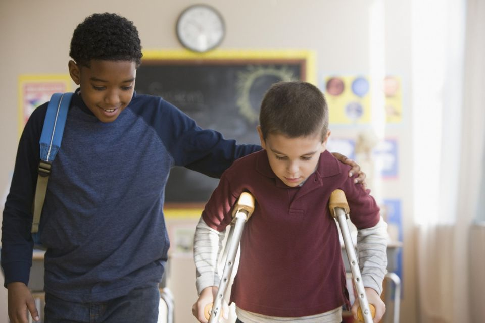 A picture of a child helping another who is on crutches