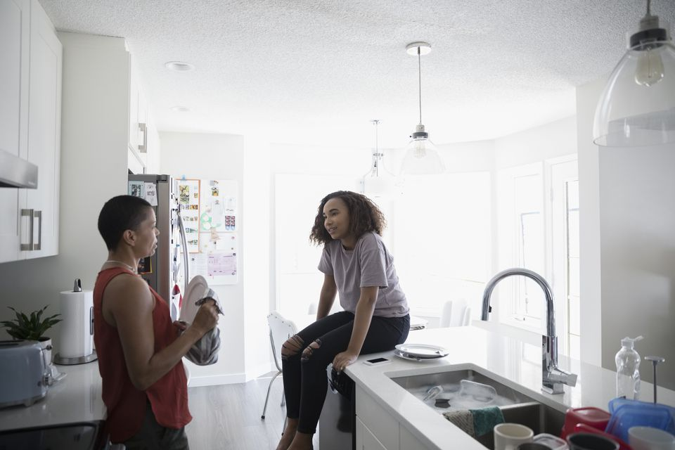 teen daughter and mom talking in kitchen