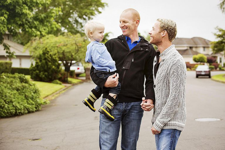 A gay couple walking with their son.